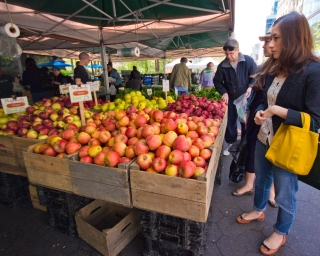 A woman looks at a display of apples at a farmers' market in New York City.