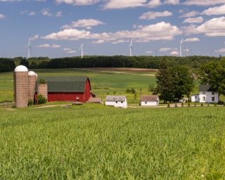 A red barn and a silo in a field, with wind turbines in the distance behind.