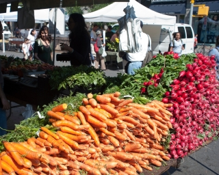 Carrots and radishes on sale at a farmers' market.