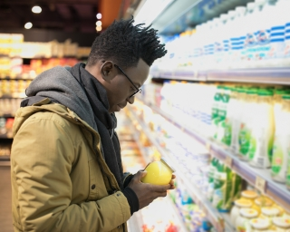 A man looks at a container of butter while in the dairy aisle of a grocery store.