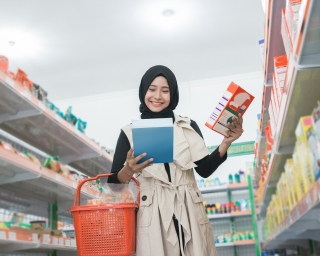 A woman buying some halal products at a supermarket.