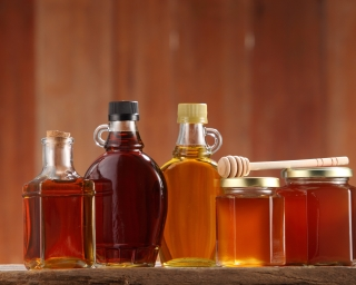 Bottles of maple syrup and honey on a table with a wooden wall behind.