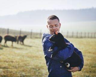 A young farmer holds a young black lamb.
