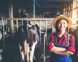 A young woman smiles and stands in front of her black and white cows.