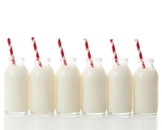 A row of milk in glass bottles with red straws