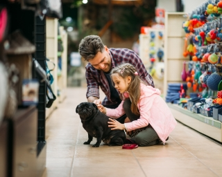 A father and daughter playing with a small black puppy on the floor of a pet store.
