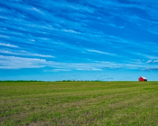 A red barn on the horizon of an open field at a farm on a sunny day in New York State.