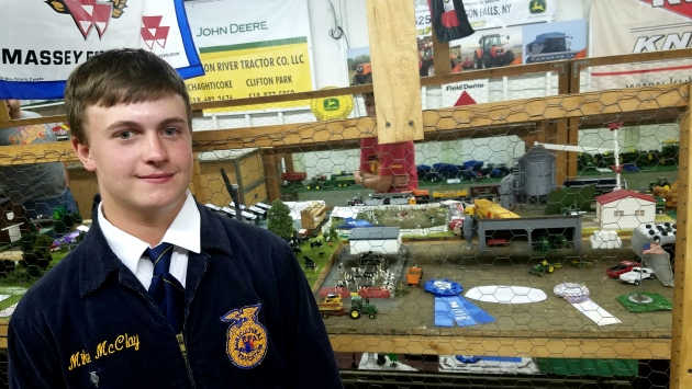 An FFA student posing next to a display at the Washington County Fair